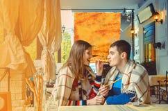 O menino e a menina em uma data e têm o divertimento que comem palitos Foto de Stock