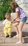 O menino e a menina em uma escada em uma cidade estacionam Fotografia de Stock Royalty Free