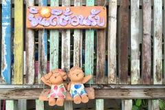 O menino e a menina emplastram as bonecas que sentam-se nos balanços que mostrando uma placa em alfabetos tailandeses Fotos de Stock