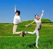 O menino e a menina estão saltando Fotografia de Stock