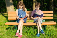 O menino e a menina estão sentando-se em um banco no livro do parque e de leitura Fotos de Stock Royalty Free