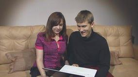 O menino e a menina estão sentando-se no sofá e estão olhando-se um portátil filme