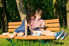 O menino e a menina estão sentando-se perto de se em um banco no p Fotografia de Stock