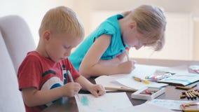 O menino e a menina estão tirando no papel por lápis da cor junto na mesa em casa vídeos de arquivo