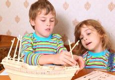 O menino e a menina fazem o barco de madeira caseiro Fotografia de Stock Royalty Free