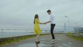 O menino e a menina felizes dançam emocionalmente algum alegre jive em um cais em uma costa de mar filme