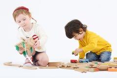 O menino e a menina felizes pequenos constroem a estrada de ferro das peças de madeira Imagem de Stock Royalty Free