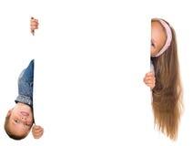 O menino e a menina felizes prendem o grande espaço em branco branco foto de stock