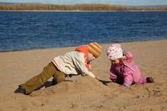 O menino e a menina jogam a areia na praia no banco de rio Foto de Stock