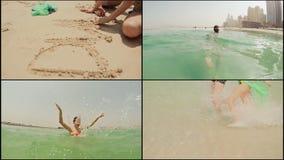 O menino e a menina jogam e nadam no mar em Dubai na praia vídeos de arquivo