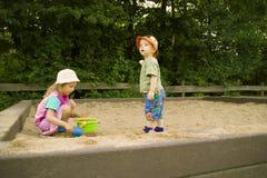 O menino e a menina jogam uma caixa de areia Fotos de Stock Royalty Free