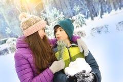 O menino e a menina na neve estacionam o fundo Foto de Stock