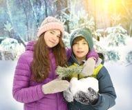 O menino e a menina na neve estacionam o fundo Imagem de Stock Royalty Free