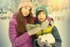 O menino e a menina na neve estacionam o fundo Imagens de Stock