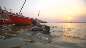 O menino e a menina nadam no Ganges no por do sol filme