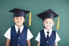o menino e a menina no tampão da graduação estão antes do quadro imagens de stock