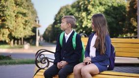 O menino e a menina novos estão sentando-se no banco vídeos de arquivo