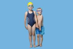 O menino e a menina novos felizes na terra arrendada do roupa de banho cedem o fundo azul Imagem de Stock