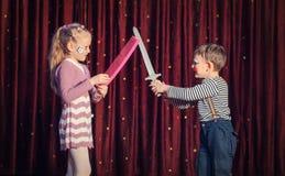 O menino e a menina que têm fingem a luta da espada na fase foto de stock royalty free