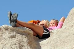 O menino e a menina relaxam na parte superior rochosa Fotografia de Stock