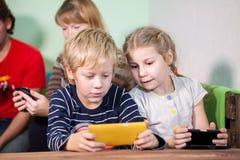 O menino e a menina são apaixonado sobre jogos em smartphones Foto de Stock
