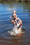 O menino e a menina são mergulhos banhados, saltam no rio. Fotos de Stock