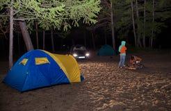 O menino e a menina sentam-se na barraca dos turistas da noite Imagem de Stock