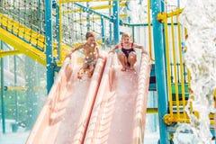 O menino e a menina têm o divertimento no parque da água foto de stock