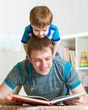 O menino e o pai da criança leram um livro no assoalho em casa Fotografia de Stock Royalty Free