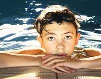 O menino em galsses da água fecha-se acima do retrato na piscina imagem de stock