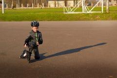 O menino em patins de rolo levanta-se após a queda fotos de stock