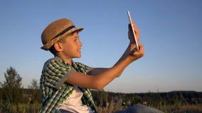 O menino em um chapéu senta-se na parte superior e nas negociações em uma comunicação video usando uma tabuleta imagem de stock