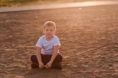 O menino em um t-shirt branco senta-se na areia imagem de stock royalty free