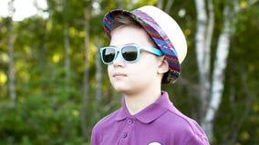 O menino em um tampão e em vidros Fotografia de Stock Royalty Free