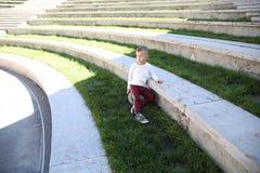O menino em um terno do esporte está sentando-se em uma bola no parque imagem de stock