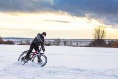 O menino em uma bicicleta no inverno está montando no gelo contra Foto de Stock Royalty Free