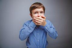 O menino em uma camisa cobriu a boca do susto com suas mãos foto de stock royalty free