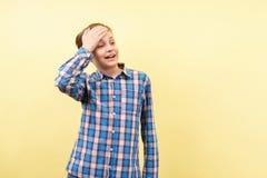 O menino embaraçado inábil cobre a testa com a mão imagens de stock