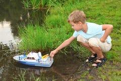 O menino emite o navio do brinquedo na flutuação Imagens de Stock Royalty Free
