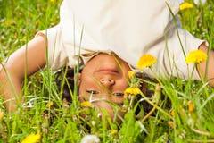 O menino encaracolado bonito está de cabeça para baixo no campo Fotos de Stock