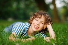 O menino encontra-se no gramado verde no parque, sustentando acima a cabeça uma mão imagens de stock royalty free