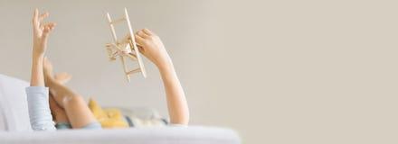 O menino encontra-se no sofá e joga-se um plano do brinquedo Imagem com um maior imagens de stock