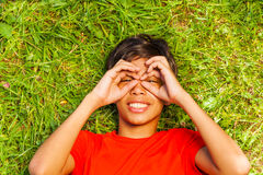 O menino engraçado com mãos na cara nos vidros dá forma Fotos de Stock Royalty Free
