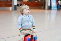 O menino engraçado da criança que vai em férias tropeça com a mala de viagem no airpo Imagem de Stock
