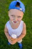 O menino engraçado em um tampão azul come um cone de gelado Imagens de Stock Royalty Free