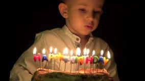 O menino engraçado eyes a vista ansioso atrás do bolo, velas de sopro do aniversário da criança vídeos de arquivo