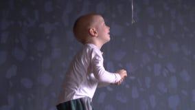 O menino engraçado na roupa azul está jogando com o balão vermelho contra a parede cinzenta A criança está feliz em casa video estoque