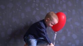 O menino engraçado na roupa azul está jogando com o balão vermelho contra a parede cinzenta A criança está feliz em casa vídeos de arquivo