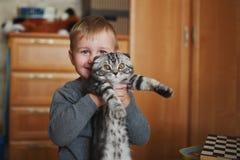 O menino engraçado pequeno abraça o gato fotografia de stock royalty free