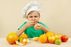 O menino engraçado pequeno come a laranja ácida na tabela com frutos fotografia de stock